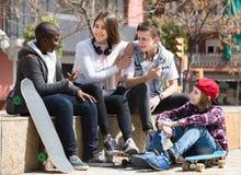 Девушка и 3 мальчика вися вне outdoors и обсуждая somethin Стоковое фото RF