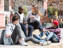 Девушка и 3 мальчика вися вне outdoors и обсуждая somethin Стоковая Фотография RF
