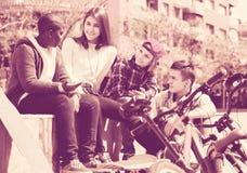 Девушка и 3 мальчика вися вне outdoors и обсуждая somethin Стоковые Изображения RF