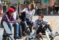 Девушка и 3 мальчика вися вне outdoors и обсуждая somethin Стоковое Изображение