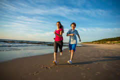 Девушка и мальчик бежать на пляже Стоковое Фото
