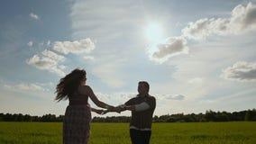 Девушка и мальчик держа руки объезжая солнце на заднем плане сток-видео