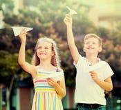 Девушка и мальчик играя бумажные самолеты Стоковое фото RF