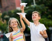 Девушка и мальчик играя бумажные самолеты Стоковая Фотография RF