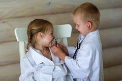 Девушка и мальчик играя доктора Стоковые Фотографии RF