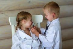 Девушка и мальчик играя доктора Стоковая Фотография RF