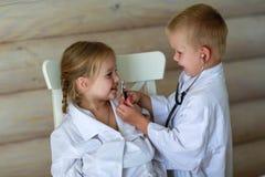 Девушка и мальчик играя доктора Стоковое Изображение