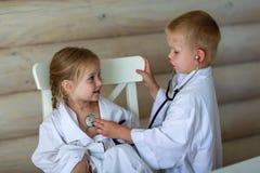 Девушка и мальчик играя доктора Стоковые Изображения RF