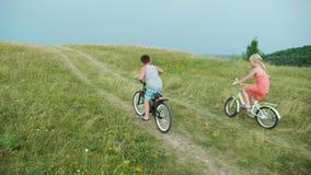 Девушка и мальчик имеют потеху ехать вверх по холму на велосипедах Состязайтесь кто сперва взбирается холм сток-видео