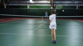 Девушка и мальчик имея спичку тенниса практикуя и тренируя на суде сток-видео