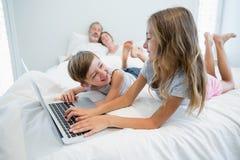 Девушка и мальчик используя компьтер-книжку на кровати в спальне дома Стоковые Фотографии RF