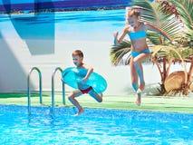 Девушка и мальчик скача в бассейн курорта Стоковая Фотография RF