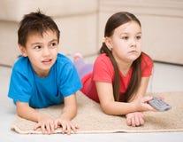 Девушка и мальчик смотря ТВ стоковые фото