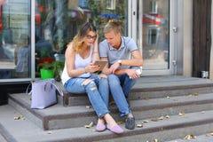 Девушка и мальчик соединяют сидеть на крылечке ресторана, беседа Стоковое Фото