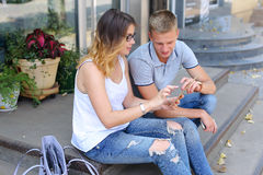 Девушка и мальчик соединяют сидеть на крылечке ресторана, беседа Стоковая Фотография
