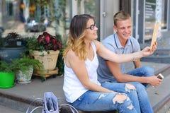 Девушка и мальчик соединяют сидеть на крылечке ресторана, беседа Стоковое фото RF