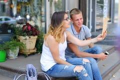 Девушка и мальчик соединяют сидеть на крылечке ресторана, беседа Стоковые Фото