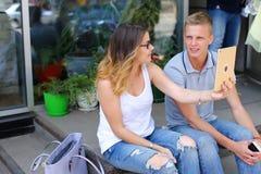 Девушка и мальчик соединяют сидеть на крылечке ресторана, беседа Стоковая Фотография RF
