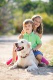 Девушка и мальчик с большой собакой в парке в лете Стоковая Фотография RF
