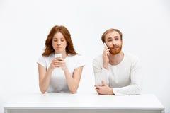 Девушка и мальчик redhead Tenderless говоря на телефонах беседуя a Стоковое Фото