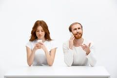 Девушка и мальчик redhead Tenderless говоря на телефонах беседуя a Стоковое Изображение