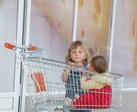 Девушка и младенец в магазинной тележкае в супермаркете Стоковые Изображения RF