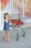 Девушка и младенец в магазинной тележкае в супермаркете Стоковое Фото