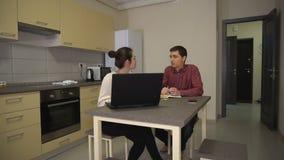 Девушка и парень говорят семейное предприятие сидя перед компьтер-книжкой видеоматериал