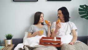 Девушка и парень есть свежие круассаны и выпивая апельсиновый сок в кровати дома сток-видео