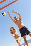Девушка и парень играя волейбол на пляже Стоковая Фотография