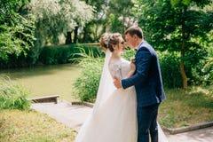 Девушка и парень как раз получили пожененными и прогулка в парке, человек плотно отжимают его любимое к нему День свадьбы внутри Стоковое Изображение RF