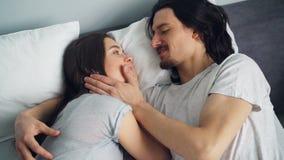 Девушка и парень обнимая говоря тереть носы в кровати в уютной квартире акции видеоматериалы