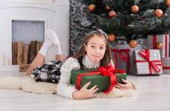 Девушка и подарок на рождество красивого ребенка внутри помещения Стоковые Фото