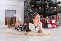 Девушка и подарок на рождество красивого ребенка внутри помещения Стоковое фото RF
