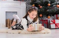 Девушка и подарок на рождество красивого ребенка внутри помещения Стоковое Изображение RF