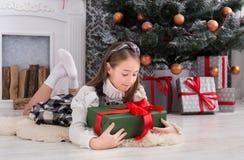 Девушка и подарок на рождество красивого ребенка внутри помещения Стоковое Фото