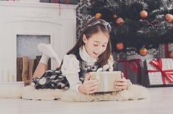 Девушка и подарок на рождество красивого ребенка внутри помещения Стоковая Фотография