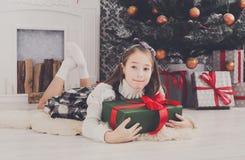 Девушка и подарок на рождество красивого ребенка внутри помещения Стоковые Фотографии RF