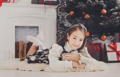 Девушка и подарок на рождество красивого ребенка внутри помещения Стоковая Фотография RF