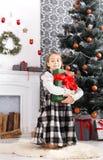 Девушка и подарок на рождество красивого ребенка внутри помещения Стоковые Изображения