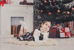 Девушка и подарок на рождество красивого ребенка внутри помещения Стоковые Изображения RF