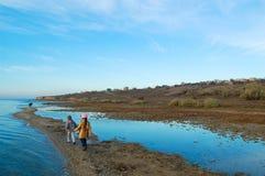 Девушка и прогулка мальчика с отцом на побережье стоковые фотографии rf