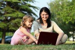 Девушка и ребенок с компьтер-книжкой Стоковые Изображения RF