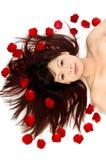 Девушка и розовые лепестки стоковое изображение