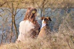 Девушка и собака в bandana сидят в траве около реки на холме вы стоковые фотографии rf