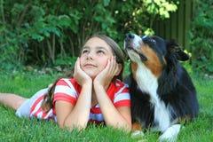 Девушка и собака лежа в траве  стоковые изображения rf