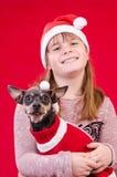 Девушка и собака ребенка в цветах рождества Стоковое Изображение