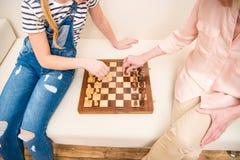 Девушка и старшая женщина играя шахмат на софе Стоковое Изображение RF