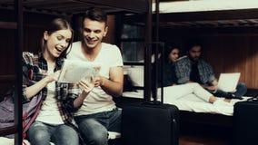Девушка и человек сидят на кровати и взгляде на карте совместно стоковые изображения rf