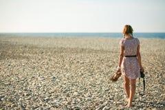 Девушка идя вдоль пляжа с камерой в руке Стоковая Фотография